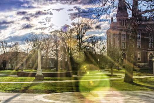 East College with sun shining through clouds