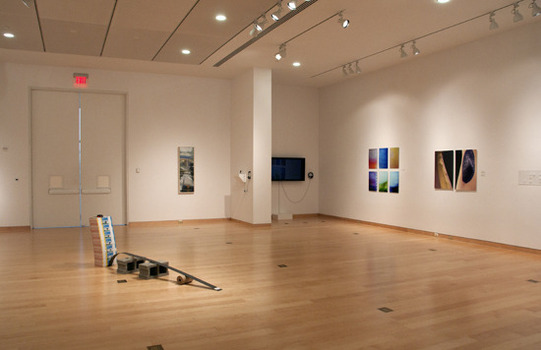 Peeler gallery with exhibit art on the wall and positioned on the floor
