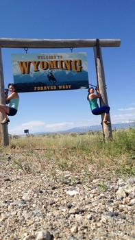 Jacquelyn at the Wyoming state line sign