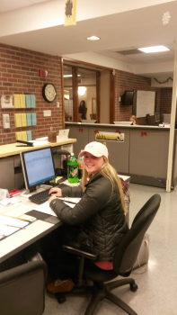 Student smiling while working at the help desk