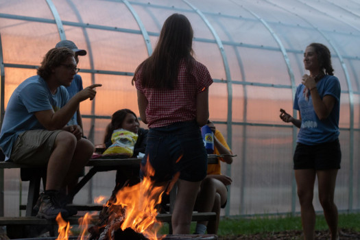 Students at the Campus Farm huddled around a campfire