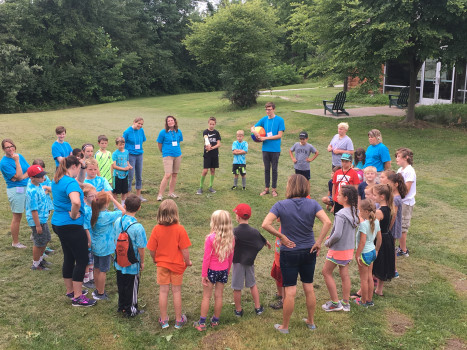 Counselors and campers gather in a circle to discuss ethics in the courtyard