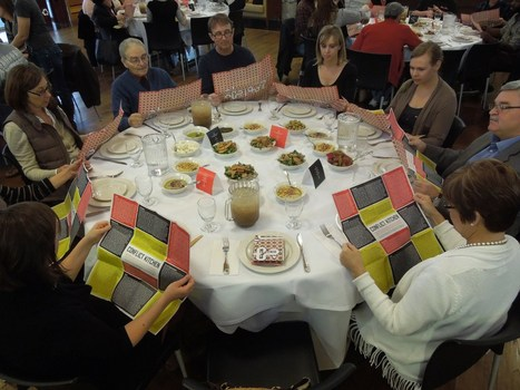 Attendees at the Conflict Kitchen dinner read food wrappers featuring interview excerpts with Palestinians about the Palestinian-Israeli conflict