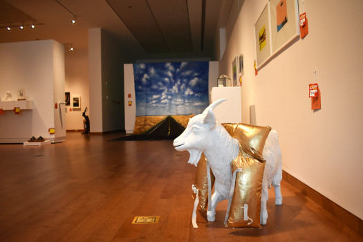 a white goat statue wearing a gold life jacket is to the right hand side with other objects visible in the background with price tags