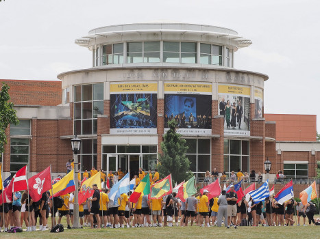 Student assembled on move-in day among the country flags in front of the Green Center