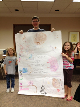 "Andrew Pfaff ('12) poses with some local Girl Scouts and their ""thank you card"" from the Order of Omega Girl Scout Cookie Drive"