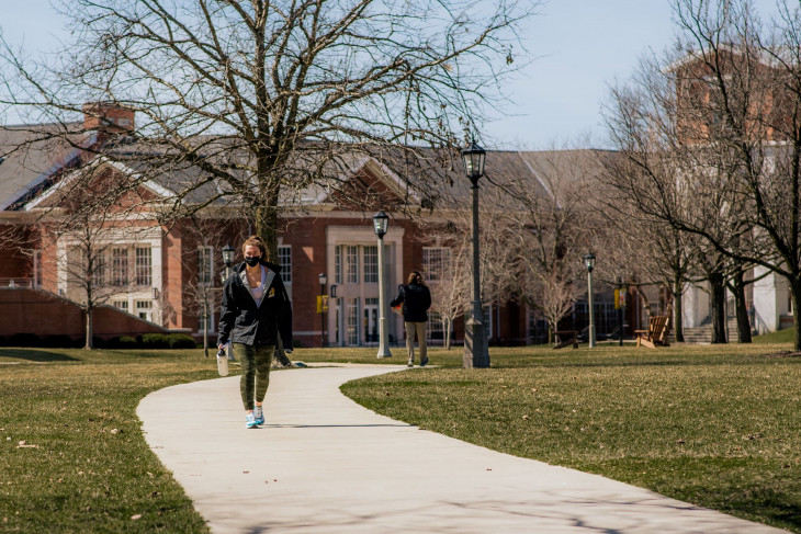Student walking along a path on campus