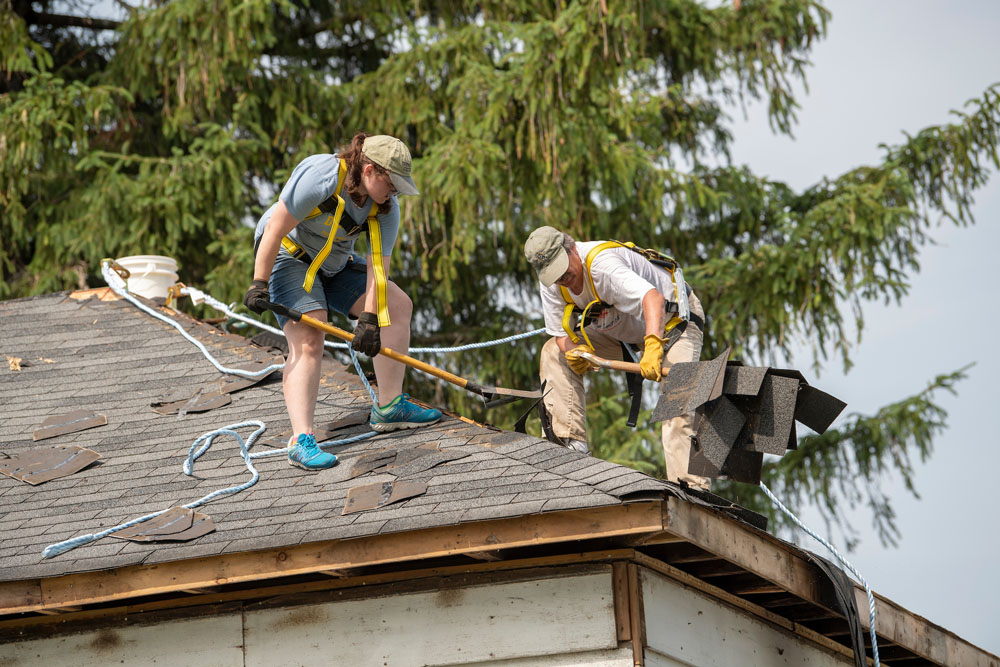 Cecilia and Prof. Mills work on removing shingles from the old farmhouse.