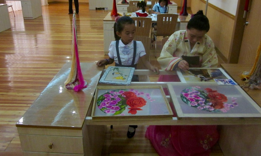 A North Korean child takes an embroidery lesson.
