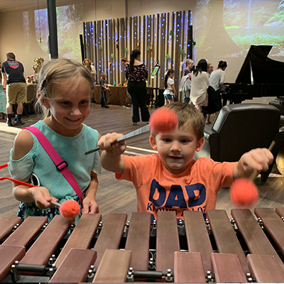 Children playing the xylophone in a community engagement activity