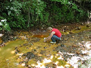 Student sampling acid-mine drainage from a seep.