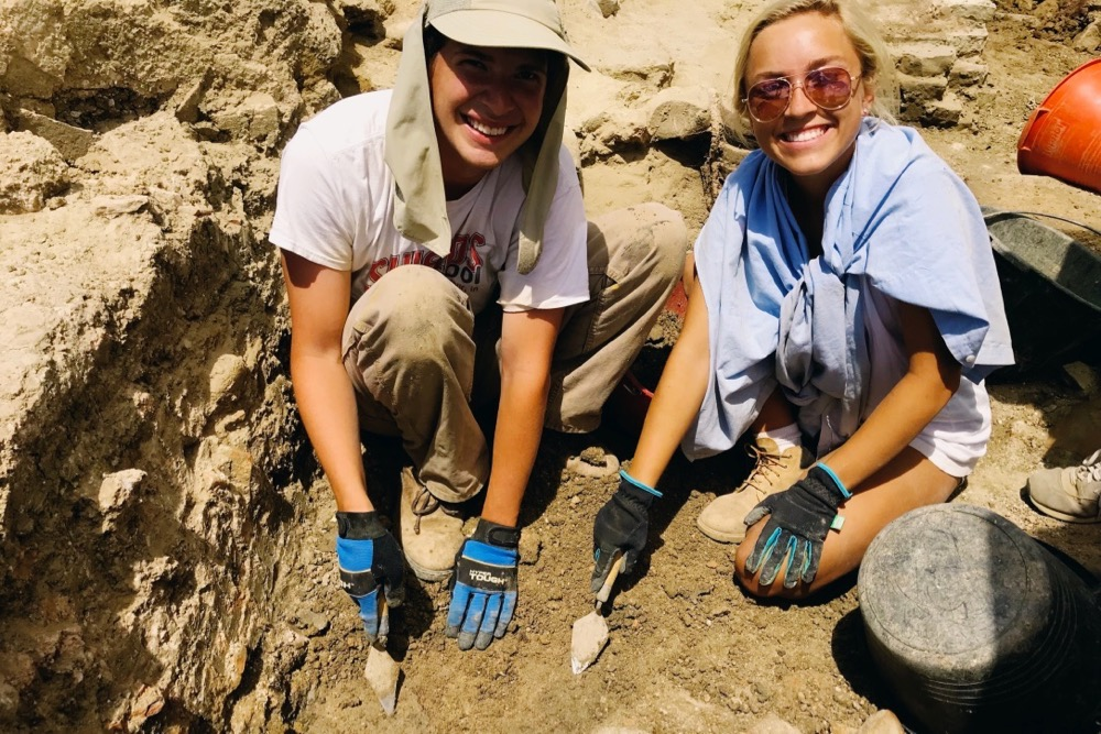Two students working in a dig trench near Lake Trasimeno