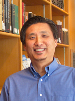 Jin Kim headshot with books in the background