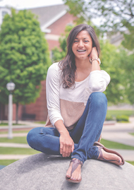 Tazree Kadam sitting on the boulder in front of East College