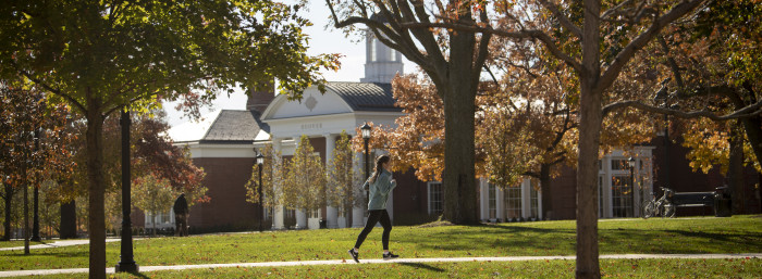 Student running on path in front of Hoover Dining Hall
