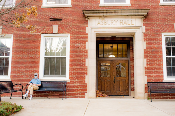 masked man sits outside Asbury Hall in the fall