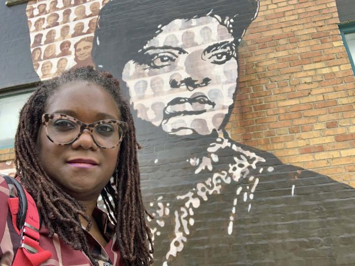 Deborah Douglas in front of mural of Ida B. Jones
