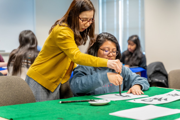 Hiroko Chiba helps a student learning Japanese calligraphy.
