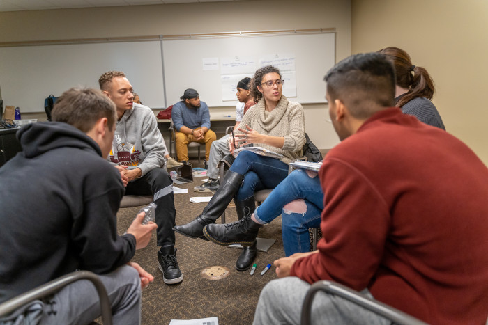 Students discuss complex issues in small groups.