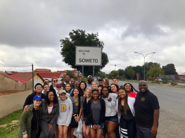 Students in front of Soweto, South Aftrica road sign