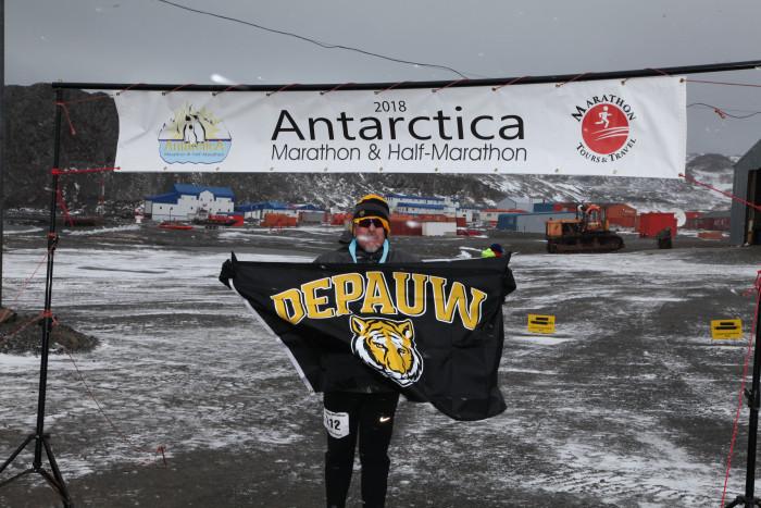 Luis Davila displays the DePauw flag in Antarctica