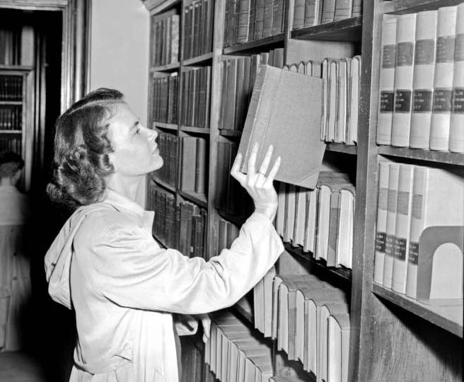 Jane Noble Luljak takes a book down from a shelf.