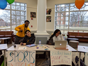 Three student coordinators at the Spring 2019 service fair recruiting volunteers for their respective programs