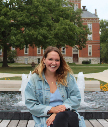 Emma Wittkowski sitting in front of the fountain in Stewart Plaza