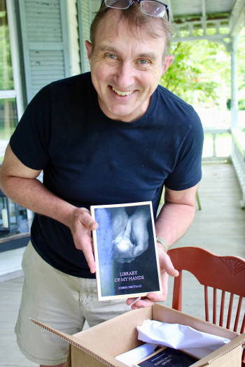 Joe Heithaus with his book of poetry