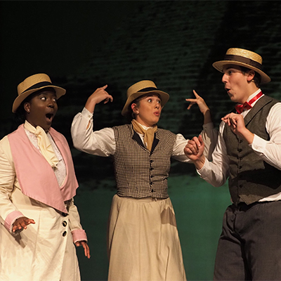 Three students performing in a musical opera