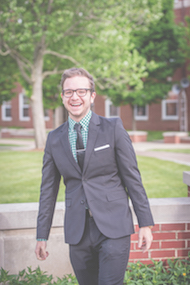 Ryan Pranger in a suit in the Holton Quadrangle