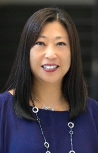 A breunette woman with long straight hair and Asian features smiling