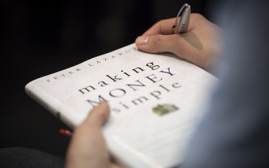 Person holding the book 'Making Money Simple' by Peter Lazaroff