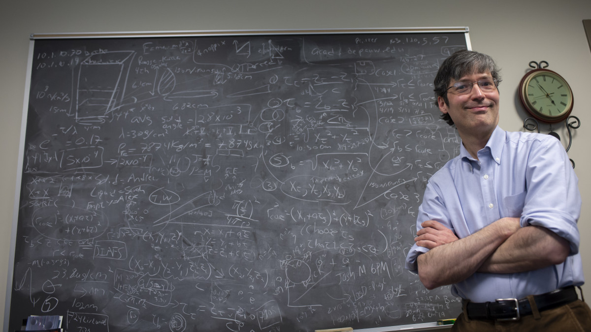 Alexander Komives poses in front of a chalkboard filled with information.