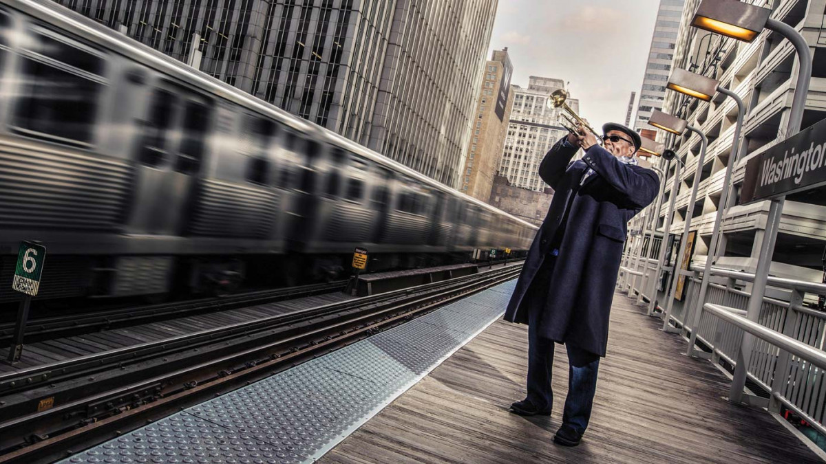 Pharez Whitted plays his trumpet beside a speeding subway train within a metropolitan scene